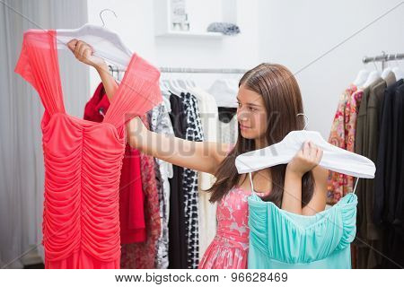 Woman having difficulties choosing dress at a boutique
