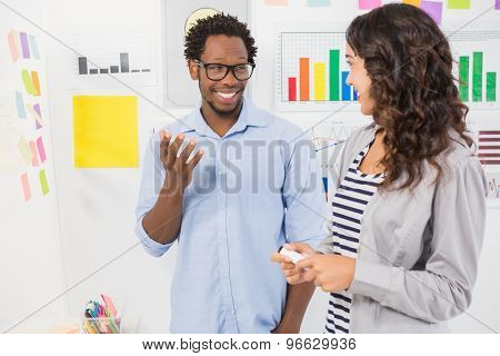 Young smiling creative business people at the office looking and talking to each other