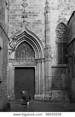 BARCELONA, SPAIN - MAR 16 2015 : A photographer kneels to take a photo outside the Cathedral.