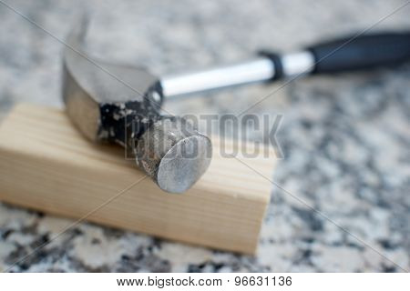 Close up of a hammer on a marble table.