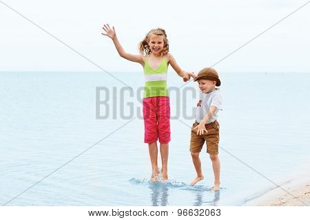 Little Boy And Girl Jumping And Having Fun. Positive Emotions.