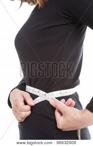 The Woman In Black Measures Her Waist Circumference With Measuring Tape On White Background.