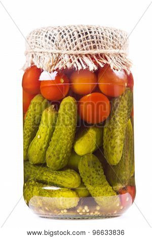 Canned Tomatoes And Pickled Cucumbers In Glass Jar