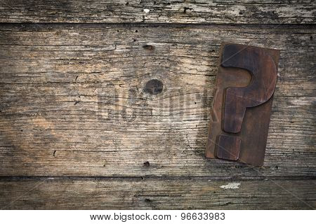 question mark vintage letterpress printing block on rustic wood background, copy space on left side