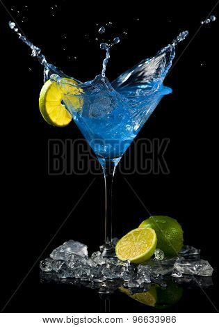 ice cube splashing in blue cocktail with lime slice, black background