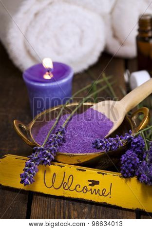 spa concept - lavender flowers, bath salt, candle, towels and welcome sign