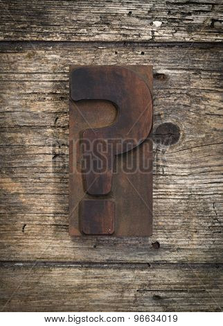 question mark vintage letterpress printing block on rustic wood background