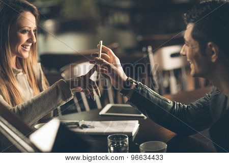 Fashionable Couple At The Bar Using A Smart Phone
