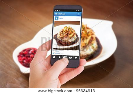 Female hand holding a smartphone against delicious duck breast dish with rice and chutney