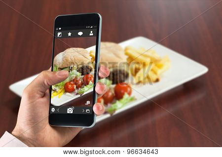 hand holding smartphone against side view of burger with french fries and salad