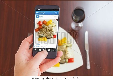 Female hand holding a smartphone against overhead view of delicious fish dish with red wine