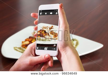 Hand holding smartphone against front view of chicken dish with salsa