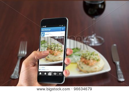 hand holding smartphone against front view of salmon dish with asparagus