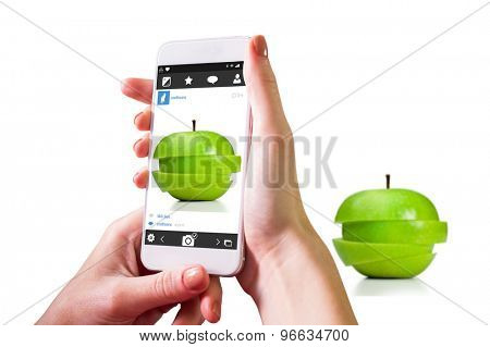 Hand holding smartphone against apple cut into slices
