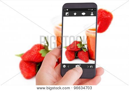 Female hand holding a smartphone against strawberry smoothie