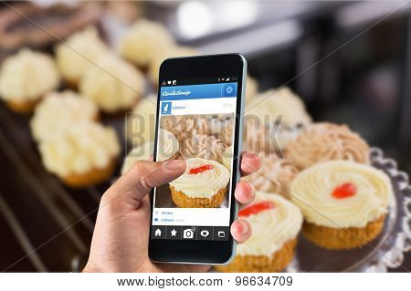 hand holding smartphone against variety of pastries at coffee shop