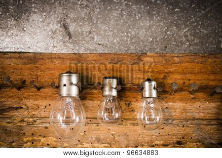 Small, Medium And Large Bulbs On The Nails On The Old Wooden Stand