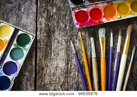 Watercolors, A Lot Of Brushes For Painting In An Old Wooden Table
