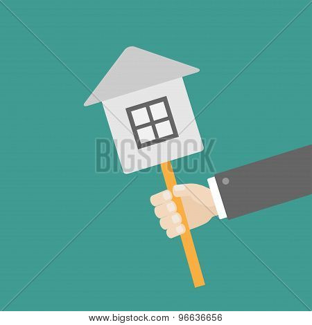 Businessman Hand Holding Paper House On The Stick Flat Design