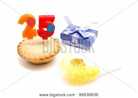 Cupcake With Twenty Five Years Birthday Candle, Whistle And Gift On White