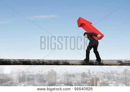 Businessman Carrying Red Arrow Sign Balancing On Tree Trunk