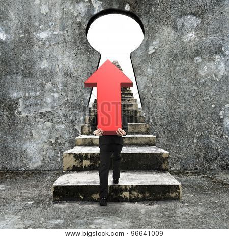 Man Carrying Red Arrow Up Climbing Concrete Stairs Toward Keyhole