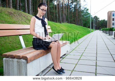 Teenage Girl Using Laptop In Park Or Campus