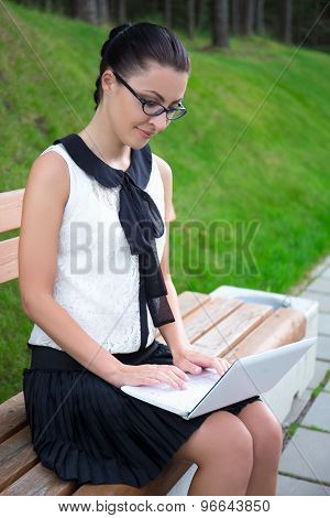 Attractive Girl In School Uniform Using Laptop In Park Or Campus