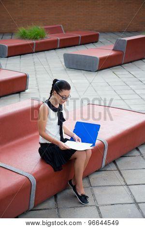 Teenage Girl Sitting On Bench And Reading Something