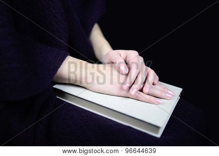 female hands on a closed book