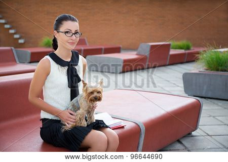 Girl Sitting With Dog Yorkshire Terrier In Park