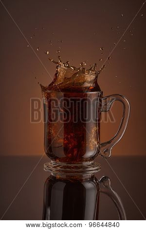 Splash of black ice coffee drink on a brown background. Liquid drink pouring into a cup w
