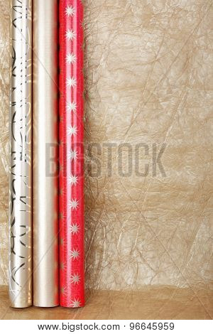 Rolls Of Multicolored Wrapping Paper For Gifts On Gold  Backgroun