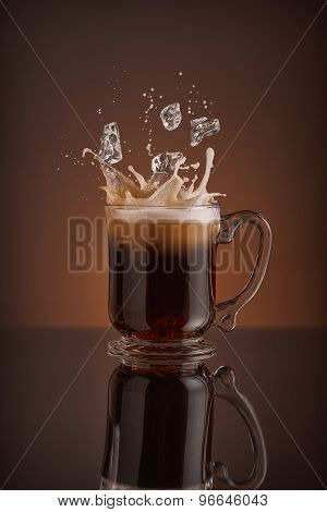 Splash of  ice coffee drink on a brown background. Refreshing Iced cappuccino liquid drink pouring i