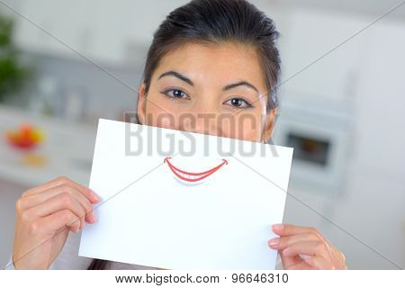 Woman holding sheet of paper over her mouth