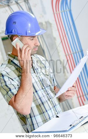 Man on building site, looking at plans, talking on cellphone