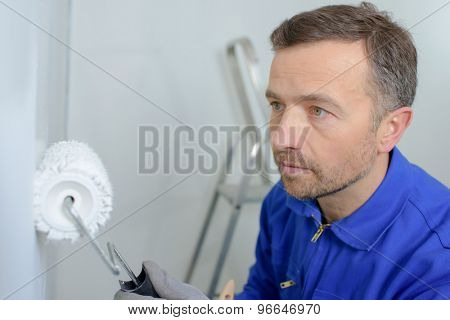 Man painting a wall white