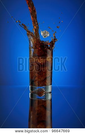Splash of cola soft drink on a blue background. Refreshing liquid drink coca pouring into a glass wi