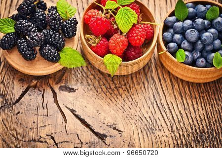 Raspberry Blueberry and Blackberry on a wood background