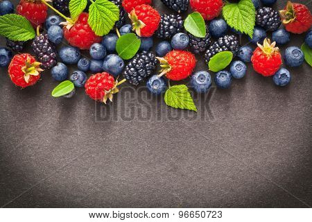 Fresh juicy berries with green leaves on dark background