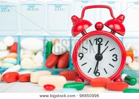 Medicine In Weekly Pill Box And Red Alarm Clock