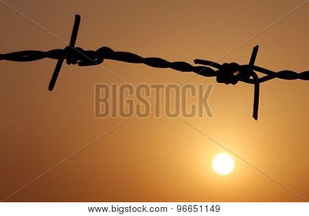 Sunset Behind A Fence Of Barbed Wire