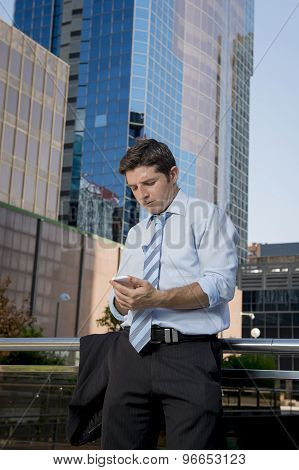 Businessman With Suit Jacket Off  In Shirt And Necktie Writing Text Message Looking At Mobile Phone