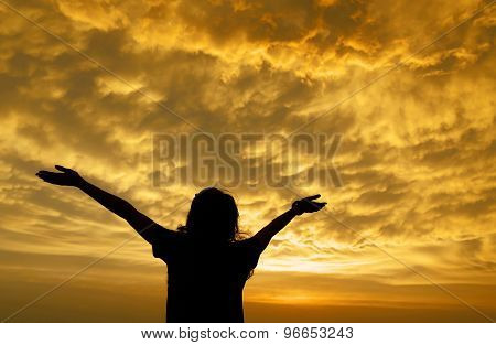 Silhouette Of A Girl Spreading Hand Toward The Clouds