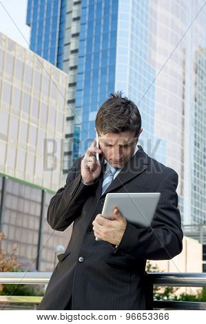 Businessman In Suit And Necktie Holding Digital Tablet Talking On Mobile Phone Overworked Outdoors A