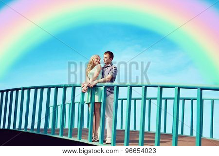 Beautiful Young Couple In Love On The Bridge Over Blue Sky And Colorful Rainbow. Valentine's Day And