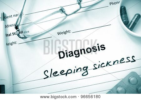 Diagnosis Sleeping sickness and tablets on a wooden table.