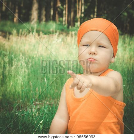 Outdoor portrait of the cute baby pointing