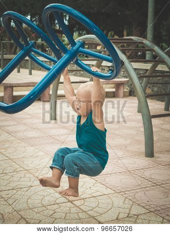 Baby doing exercises on a playground. Toned