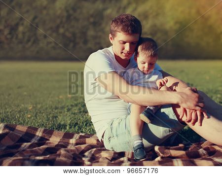 Portrait Of Happy Father And Son Child Together Resting Outdoors On The Grass Warm Summer Evening